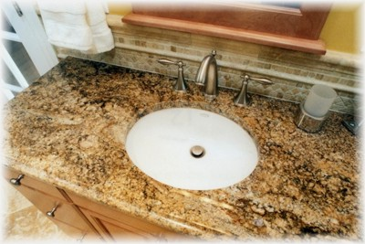 One of two undermounted bowls, traditional satin nickel faucets and  7' granite countertop over a  maple vanity & matching decorative framed mirrors